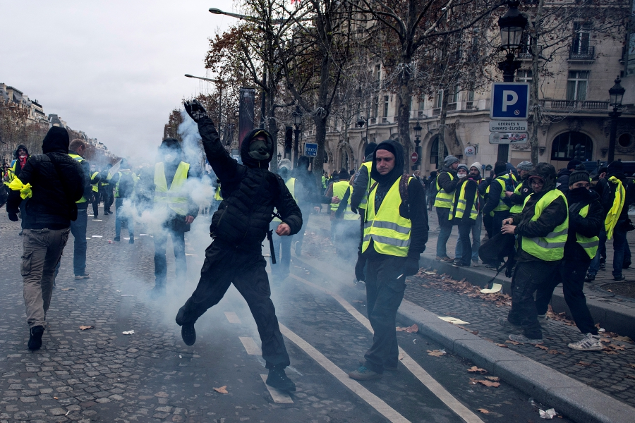 A Yellow Vests protester hurls an object to police forces during a demonstration in Paris, France, 08 December 2018. Police in Paris is preparing for another weekend of protests of the so-called 'gilets jaunes' (yellow vests) protest movement. ( EPA/JULIEN DE ROSA)