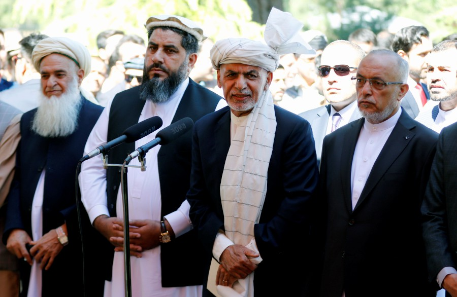 Afghan president Mohammad Ashraf Ghani (centre) talks with journalists after Eid al-Fitr prayer at the presidential palace in Kabul, Afghanistan. - EPA