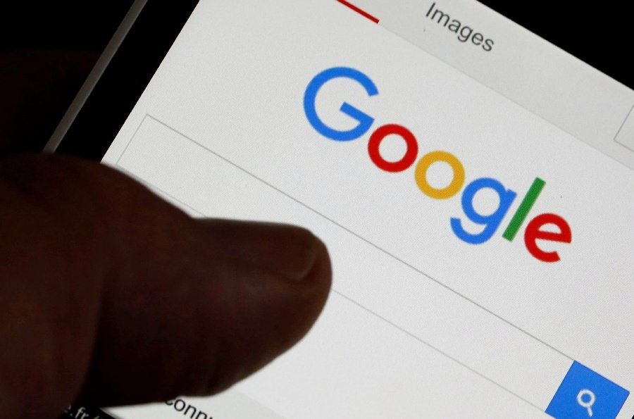 A man holds his smartphone which displays the Google home page. REUTERS