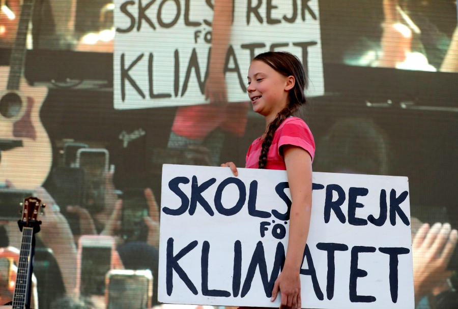 Sixteen year-old Swedish climate activist Greta Thunberg carries a sign onto the stage at the Global Climate Strike in lower Manhattan in New York. - EPA