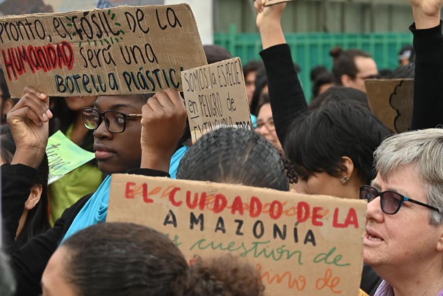 """People protest with signs in Lima, Peru in the framework of the """"Friday for the planet"""" global demo against climate change.- AFP"""