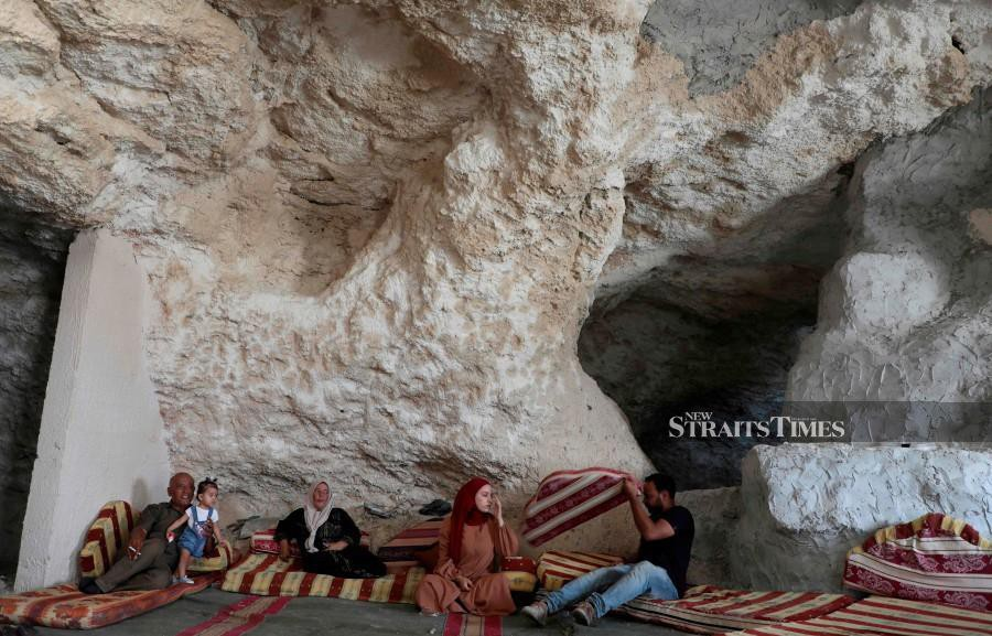 Ahmed Amarneh (right), and family members sit on cushions at his home built in cave, in the village of Farasin, west of Jenin, in the northern occupied West Bank. AFP photo