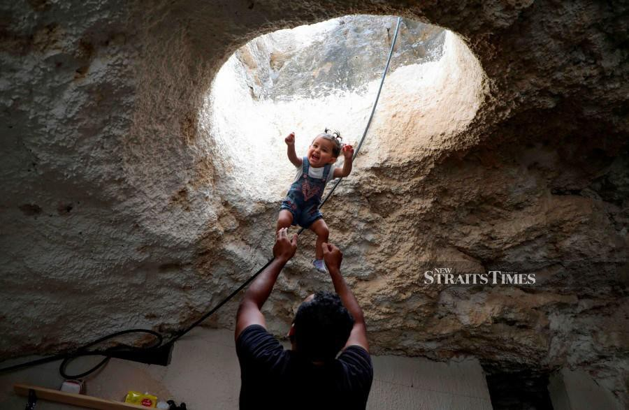 Ahmed Amarneh throws his daughter beneath a skylight hole as they play together at his home. AFP photo