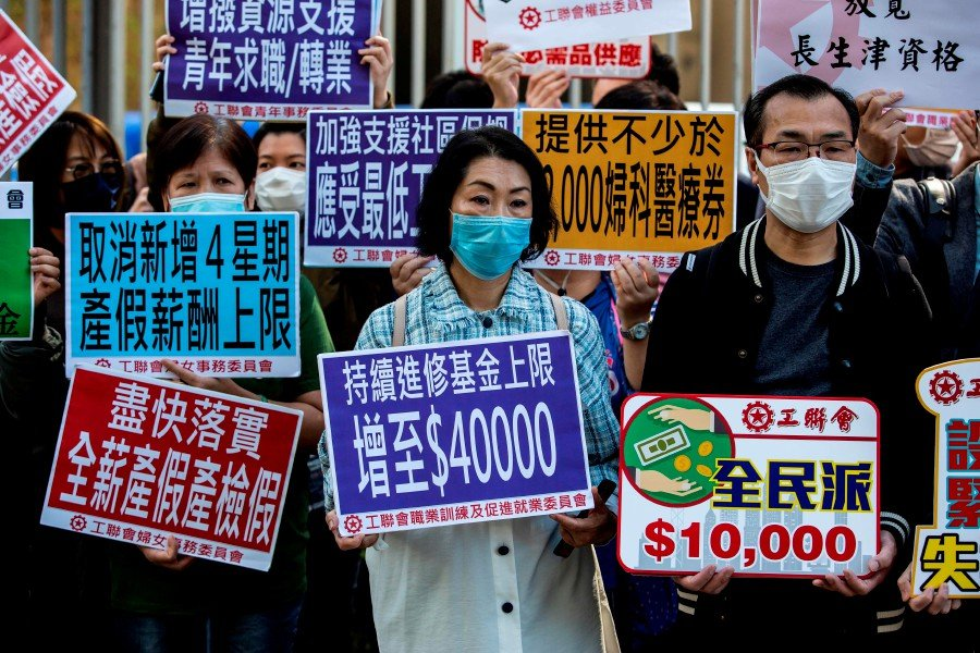 Members of community groups protest before Hong Kong Financial Secretary Paul Chan delivers the annual budget at the legislative council in Hong Kong. - AFP