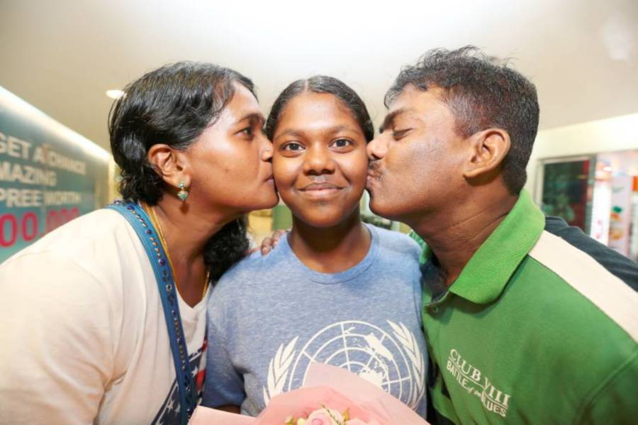 Mother S. Jaya Devi, 44, (left) and her father R. Ramakrishnan, 50, kissing her daughter R. Prevena, 14, when arriving at Penang International Airport (PIA), Bayan Lepas here today. Prevena made it to the 2017 International Model United Nations conference in the United States, a first for any student in the country. She was awarded the Best Speaker and Best Position Paper awards based on her presentations on two topics. Pic by NSTP/MIKAIL ONG