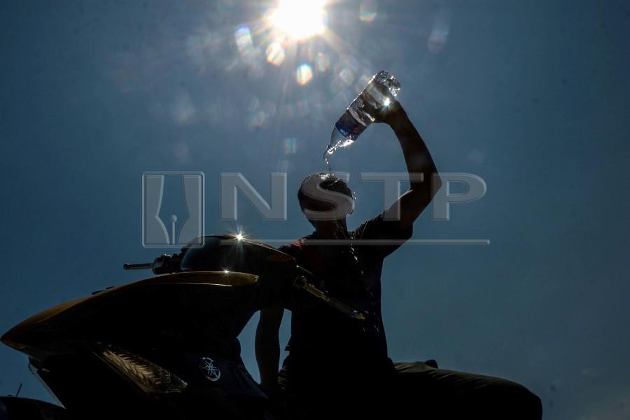 Abu Umair pours water onto himself following the hot weather in Penang. -NSTP/SHAHNAZ FAZLIE SHAHRIZAL