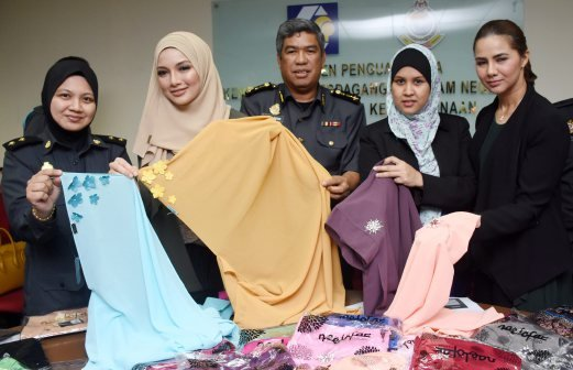 Selangor Domestic Trade, Cooperatives and Consumerism enforcement chief Abdul Rosik Yakub with his officers and Neelofa showing the original and fake Naelofar Hijab headscarves during a press conference today. Pix by Mohd Asri Saifuddin Mamat