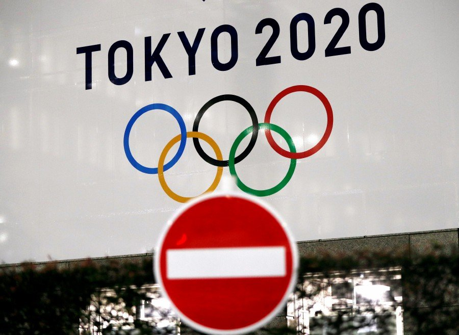 A banner for the upcoming Tokyo 2020 Olympics is seen behind a traffic sign, following an outbreak of the coronavirus disease (COVID-19), in Tokyo, Japan. -REUTERS pic