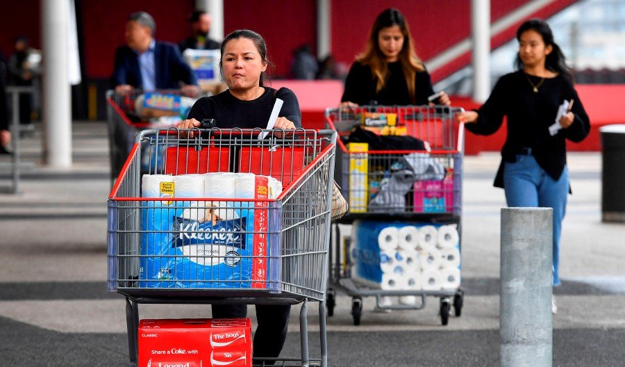 People leave a Costco warehouse with rolls of toilet paper amongst their groceries in Melbourne. - AFP pic