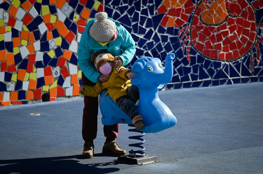 A woman puts a face mask on a boy as he plays at a playground along a street in Beijing on Feb 22, 2020. Photo: AFP