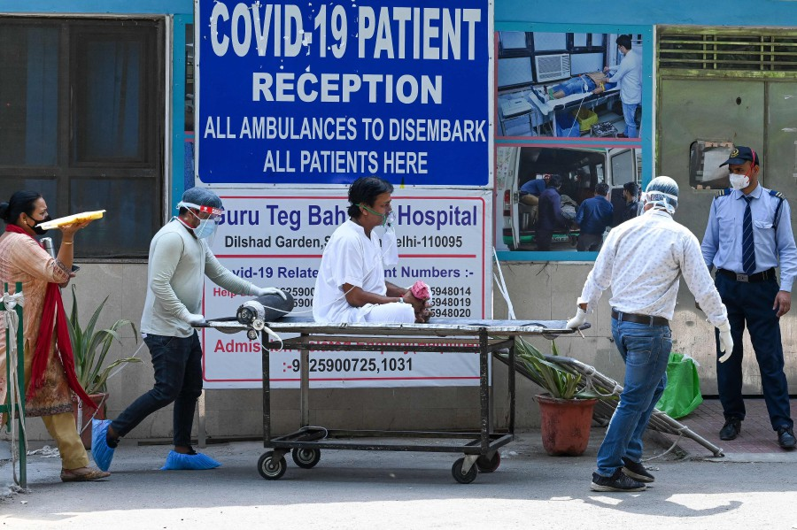 A Covid-19 coronavirus patient is shifted to ward after admission at GTB hospital in New Delhi. - AFP pic