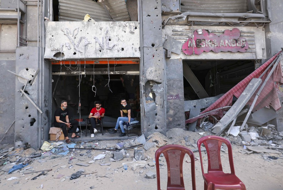 Palestinian shop owners sit at the entrance of their damaged store in the al-Rimal commercial district in Gaza City. - AFP pic