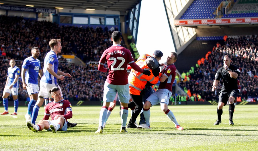 A fan is restrained by a steward and Aston Villa's Glenn Whelan after invading the pitch and attacking Aston Villa's Jack Grealish during the match. - Reuters
