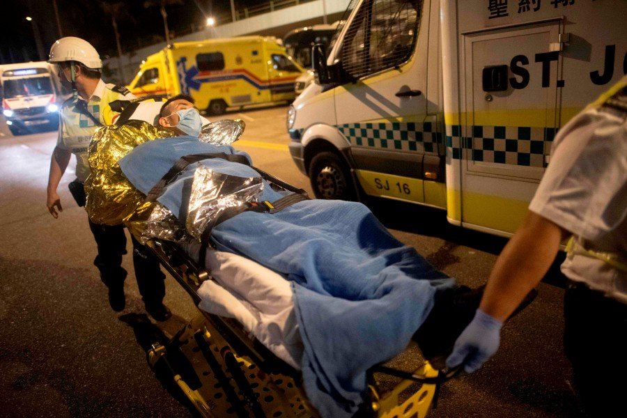 A protester is taken away on a stretcher outside the Hong Kong Polytechnic University campus in the Hung Hom district of Hong Kong. - AFP