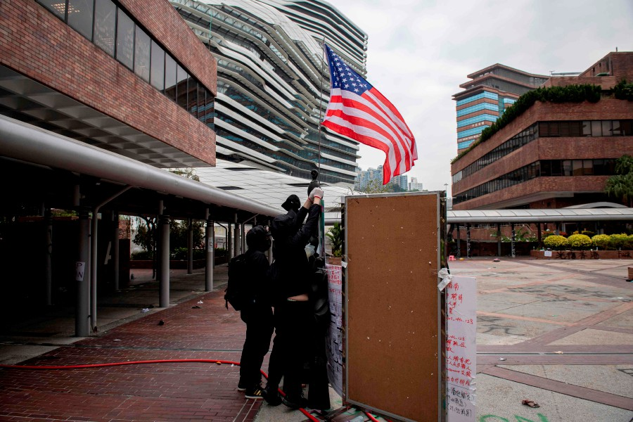 Protesters raise a US flag inside the Hong Kong Polytechnic University in the Hung Hom district of Hong Kong. - AFP
