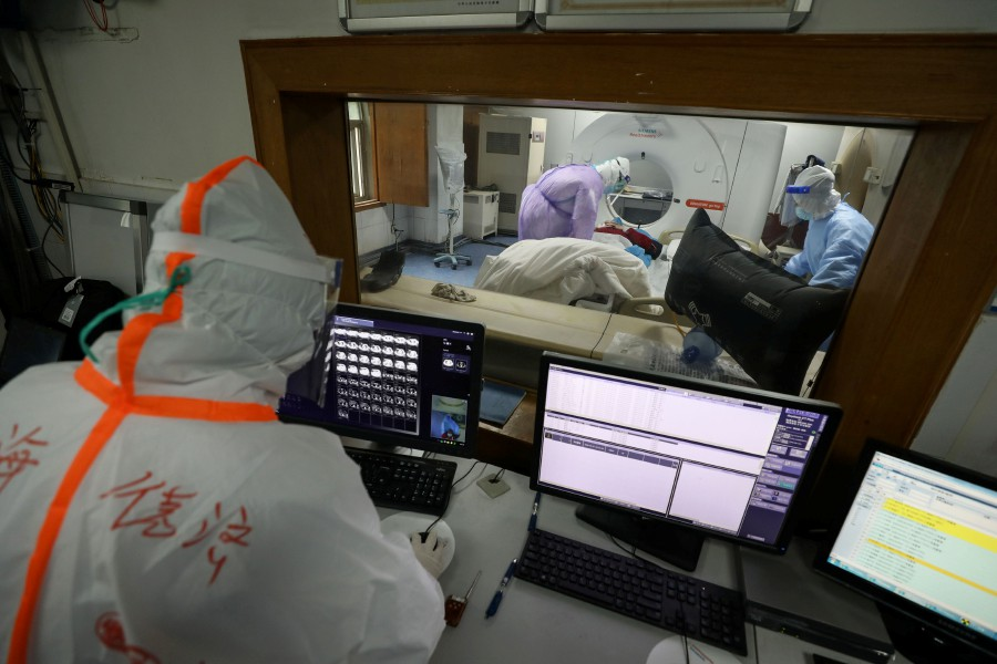 This photo taken on February 28, 2020 shows a medical staff member looking at a screen as a patient infected by the COVID-19 coronavirus does a CT scan at the Red Cross hospital in Wuhan in China's central Hubei province. - AFP pic