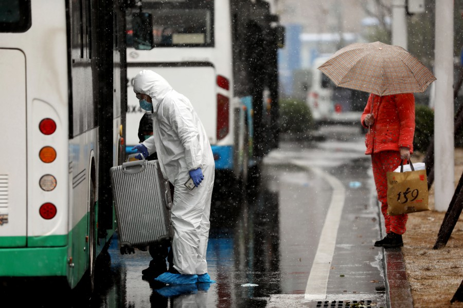 A worker in protective suit lifts a suitcase from a bus amid snow to help transport novel coronavirus patients outside a hospital in Wuhan, Hubei province, China. -China Daily via Reuters