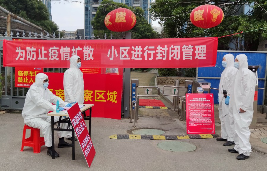 Workers in protective suits are seen at a checkpoint for registration and body temperature measurement, at an entrance to a residential compound in Wuhan, the epicentre of the novel coronavirus outbreak, in Hubei province, China. -China Daily via Reuters