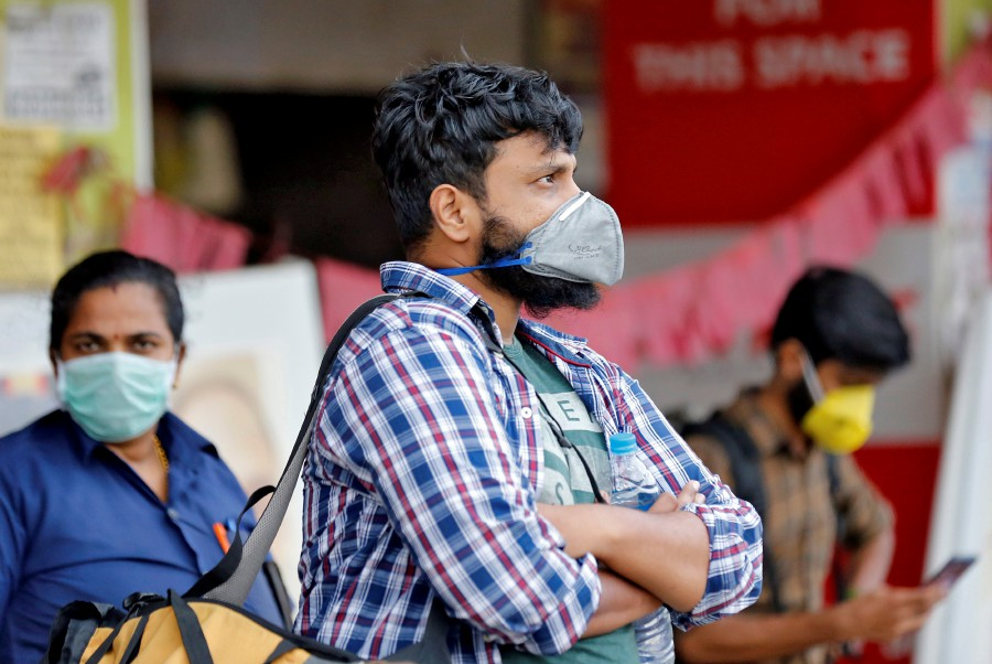 People wearing protective masks wait to board a bus at a terminal amid coronavirus fears, in Kochi, India. -REUTERS pic