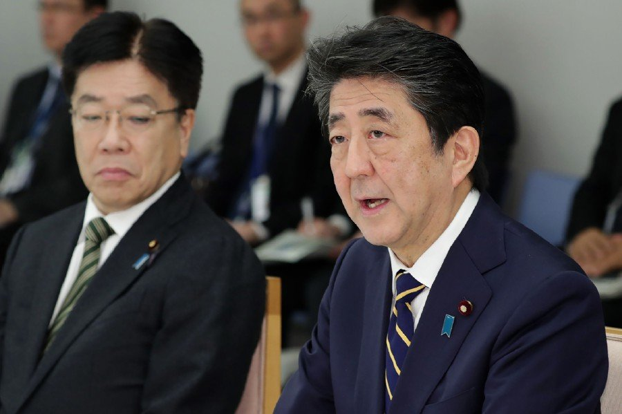 Japan's Prime Minister Shinzo Abe (right) and Health Minister Katsunobu Kato (left) attend a meeting at the new COVID-19 coronavirus infectious disease control headquarters at the prime minister's office in Tokyo. -AFP
