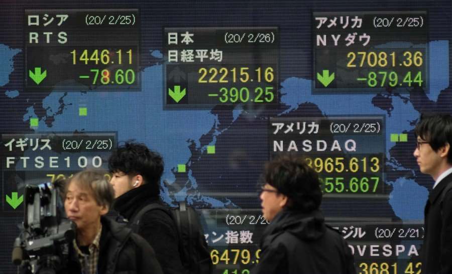 Pedestrians walk past an electronic quotation board displaying share prices of the Nikkei 225 Index (C, top) and other global stock markets in Tokyo. -AFP