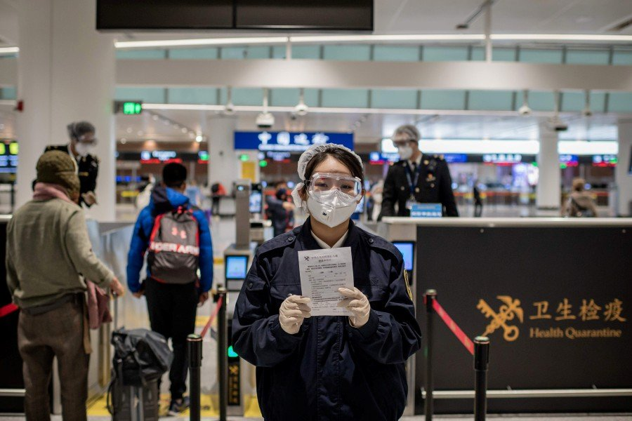 This picture taken on February 14, 2020 shows a health quarantine officer (centre) wearing protective gear as she holds a health document to be filled and signed by arriving passengers in the wake of the COVID-19 coronavirus outbreak before passing customs at Daxing international airport in Beijing. -AFP