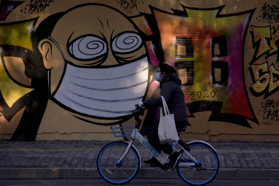 A woman wearing a protective mask cycles past graffiti-painted wall at a construction site in Shanghai, China, as the country is hit by coronavirus outbreak. -Reuters