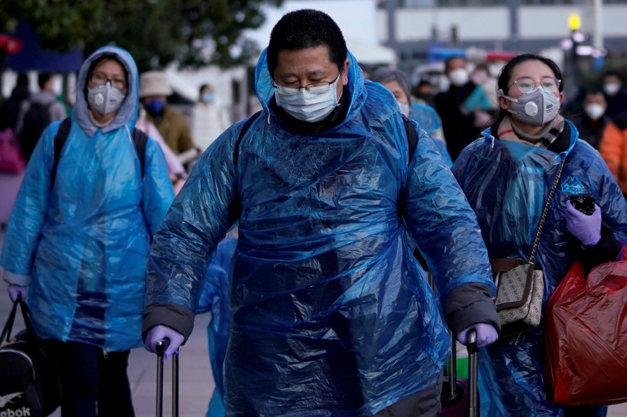People wear face masks and plastic raincoats as a protection from coronavirus at Shanghai railway station, in Shanghai, China. -Reuters