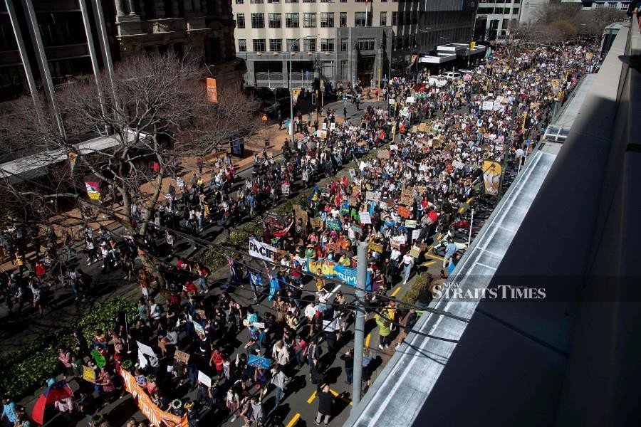 Protesters march to Parliament down Lampton Quay during a climate strike protest march in Wellington. - AFP