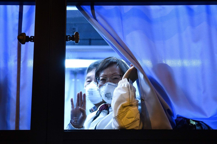 A US passenger waves to reporters while arriving at the Haneda Airport, in Tokyo on February 17, 2020 after disembarking in Yokohama from the Diamond Princess cruise ship, where people are quarantined onboard due to fears of the new Covid-19 coronavirus. - AFP