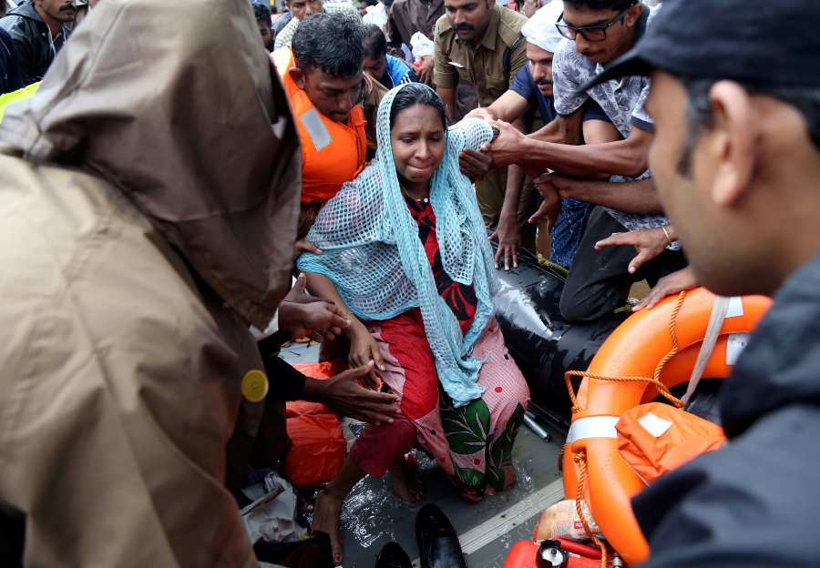 Rescuers help a pregnant woman to disembark a boat after she was evacuated from a flooded area in Aluva in the southern state of Kerala, India, August 18, 2018. REUTERS