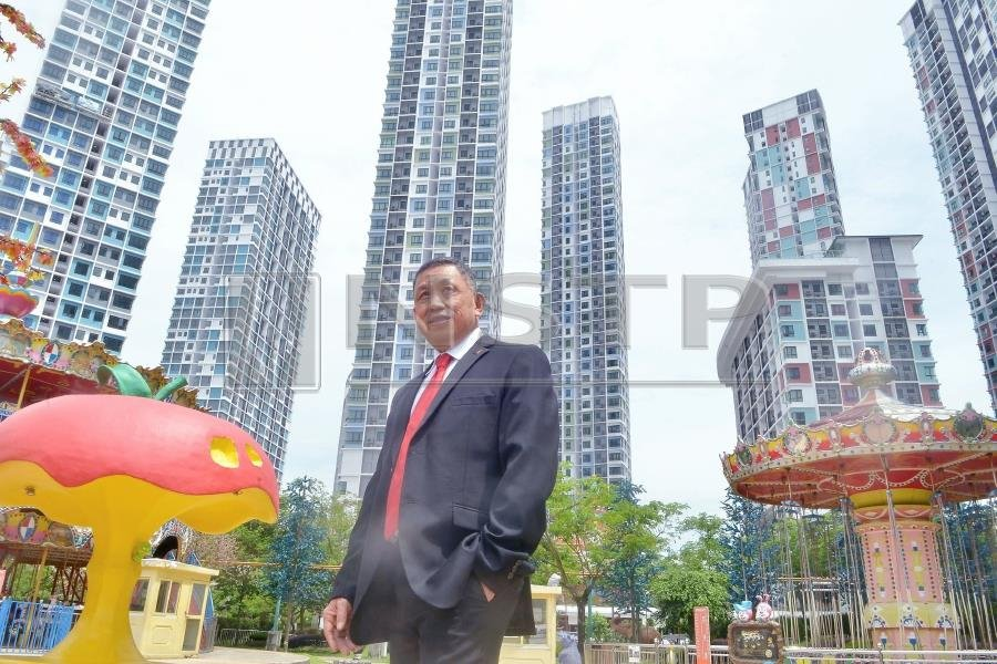 I-Berhad group executive chairman Tan Sri Lim Kim Hongstanding proudly a mong the tall structures he built in i-City.