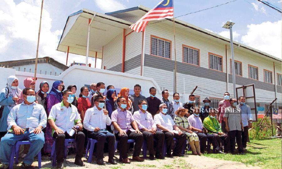Dr Radzi Jidin (seated, centre) with teachers and parent-teacher association members of SK Merampong in Keningau.