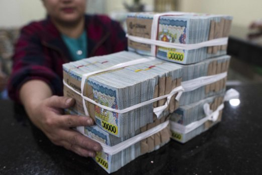 File Pix A Banker With Stack Of Myanmar Kyat Notes At The Bank In Yangon Is Spinning Through Thrilling Economic Revival Since Shedding Junta