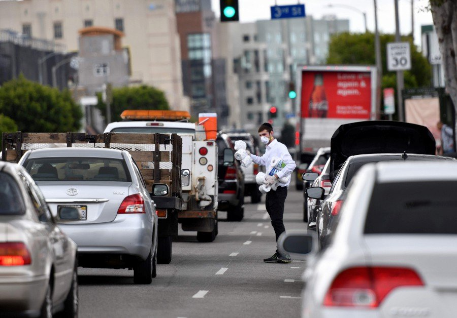 A man offers toilet paper and paper towels for free (1 roll per family) from the back of his car in Los Angeles. AFP