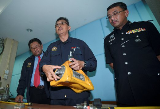South Klang district police chief Assistant Commissioner Alzafny Ahmad (right) listens as Atomic Energy Licensing Board (AELB) Malaysia senior assistant engineer Zulkefle Hussin (centre) explains how the special device detects radioactive materials. Pix by MUHAMMAD SULAIMAN.