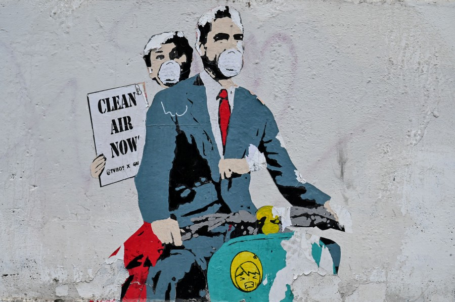 """A mural by street artist """"TV Boy"""" depicting a famous film """"Roman Holiday"""" with Gregory Peck and Audrey Hepburn as she holding a banner reading """"Clear Air Now"""" is displayed on a wall near ancient Colosseum, in central Rome during the Covid-19 outbreak. AFP"""
