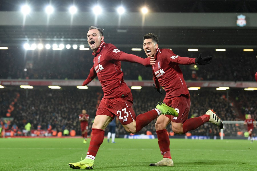 Liverpool's Swiss midfielder Xherdan Shaqiri celebrates with Liverpool's Brazilian midfielder Roberto Firmino (R) after scoring their third goal during the English Premier League football match between Liverpool and Manchester United at Anfield in Liverpool. (Photo by AFP)