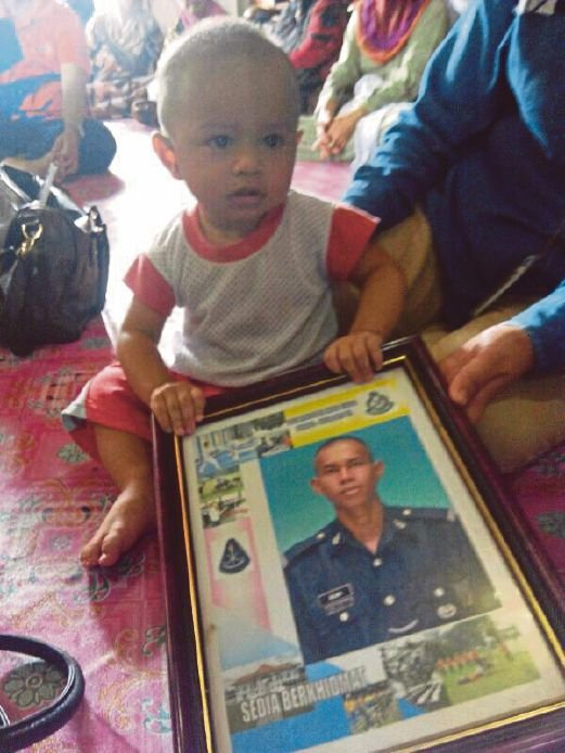 Corporal Abd Rajah Jamuan's only child, Khairil Zafran, 12 months, holding a picture of his father at his home in Batu 2, SempornaPix by Abdul Rahemang Taiming