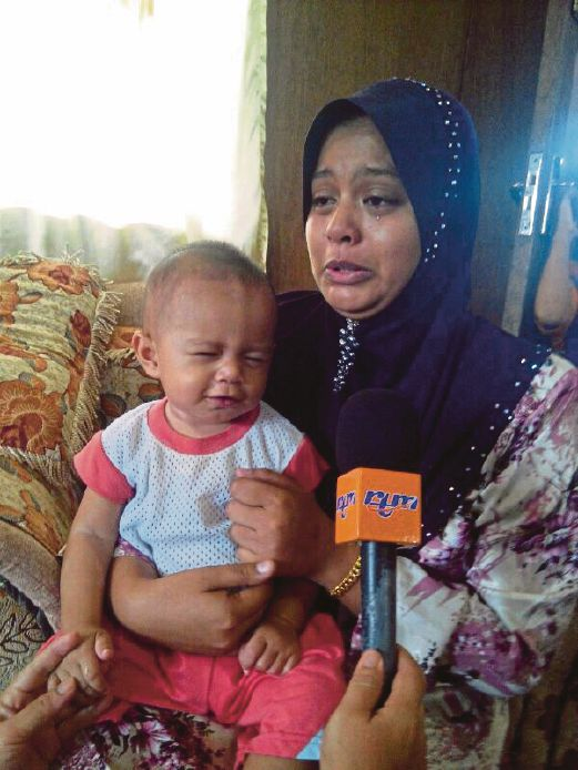 Corporal Abd Rajah Jamuan's wife, Salamah Amad, 26, holding their only child, Khairil Zafran, 12 months when interviewed by the media at her home in batu 2, Semporna.Pix by Abdul Rahemang Taiming