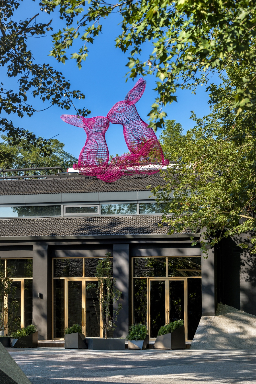 The kissing rabbits made out of wire mesh sit atop the Pink Rabbit Restaurant.