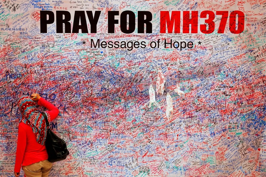 A woman leaves a message of support and hope for the passengers of the missing Malaysia Airlines MH370 in central Kuala Lumpur on March 16, 2014. - Reuters/File Photo