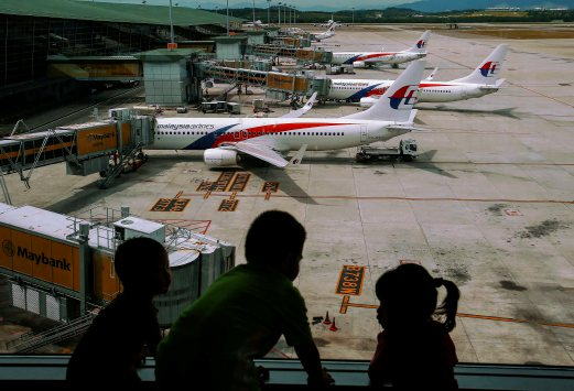 Children look at Malaysia Airlines Boeing 737-800 aircrafts parked at Kuala Lumpur International Airport (KLIA)outside Kuala Lumpur June 14, 2014. Sunday marks the 100th day that Malaysian Airlines Flight MH370 from Kuala Lumpur to Beijing disappeared with 239 passengers and crew on board. REUTERS