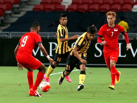 Malaysia's Nazirul Naim (centre) is challenged by Singapore's Faritz Hameed (left) and Gabriel Quek. Pix by HAIRUL ANUAR RAHIM.
