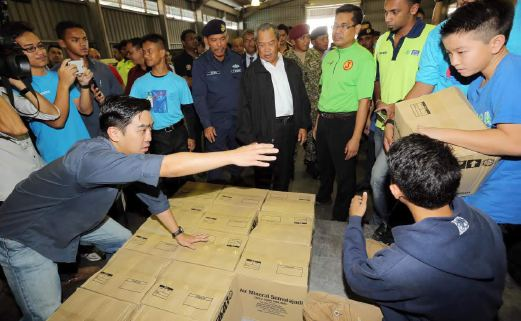 Deputy Prime Minister Tan Sri Muhyiddin Yassin inspecting flood relief effort by volunteers at the Subang Air Force base -- Pix by Abdullah Yusof