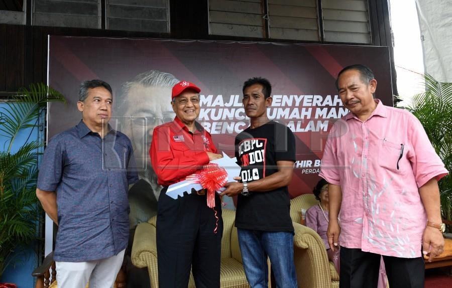 Tun Dr Mahathir Mohamad presenting a mock key to Zamberi Muhammad Akhir, whose house was badly damaged in a storm two months ago. Zamberi's family was among 46 families whose houses were rebuilt following the Aug 23 storm. All received the keys to their homes from the prime minister today. (BERNAMAPIC)