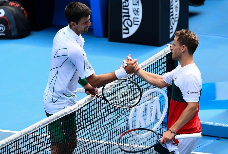 Argentina's Diego Schwartzman (right) congratulates Serbia's Novak Djokovic after their men's singles match on day seven of the Australian Open tennis tournament in Melbourne. -AFP