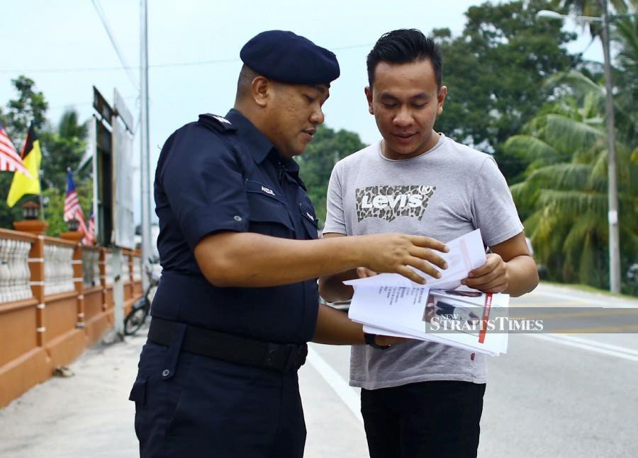 A policeman handing out a missing person notice to locals in Seremban. -NSTP/Adzlan Sidek