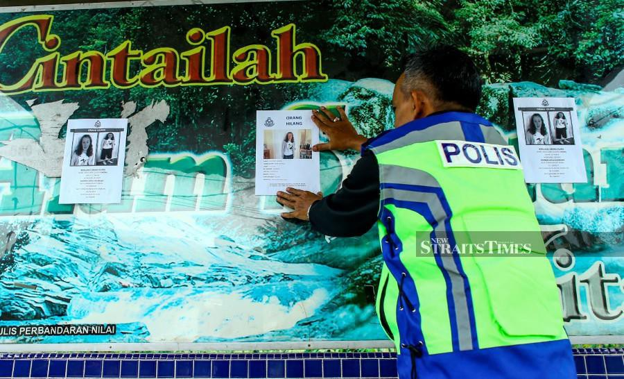 A policeman putting up a missing person notice in Seremban following the disappearance of the teenager in Seremban. -NSTP/Adzlan Sidek
