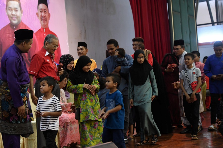Prime Minister Tun Dr Mahathir Mohamad and wife Tun Dr Siti Hasmah Mohamad Ali handing out duit raya at the Langkawi Parliamentary Constituency's Hari Raya Open House today. - Bernamapic